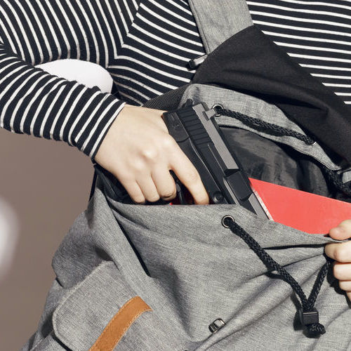 A Woman Takes a Pistol From Her Backpack.